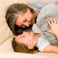 Grandmother with granddaughter hugging on sofa Stock Photos