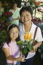Grandmother and granddaughter in plant nursery holding flowers portrait Stock Photo