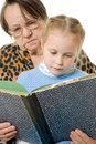 Grandmother granddaughter reading a book Stock Photos