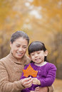 Grandmother and granddaughter smiling and looking at leaf together Royalty Free Stock Photography