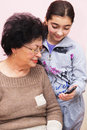 Grandmother and granddaughter young showing a mobile phone to her light pink background focus on young girl Royalty Free Stock Image