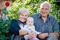 Grandmother and Grandfather holding their little boy