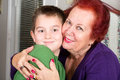 Grandmother and grandson cheek to cheek hug s love her eight years old she hugs him tighly with a touch while looking at you Stock Photography