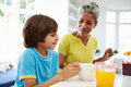 Grandmother and grandson having breakfast together in kitchen sitting at table Royalty Free Stock Images