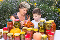 Grandmother with grandson and home canned vegetables her Royalty Free Stock Photography