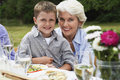 Grandmother with grandson sitting at table in garden portrait of happy young boy dining Stock Photo