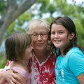 Grandmother happy kissing her two granddaughters with a funny expression Stock Photo