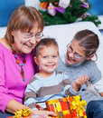 Grandmother and her two grandchildren with gifts Royalty Free Stock Photos