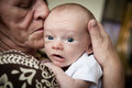 Grandmother holding baby kissing cute newborn grandson Royalty Free Stock Image