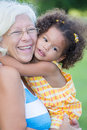 Grandmother hugs her hispanic granddaughter and laughs with a diffused green grass background Stock Image