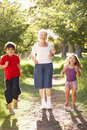 Grandmother Jogging In Park With Grandchildren Stock Photo