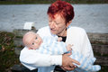 Grandmother kissing grandson holding infant outside Stock Photo