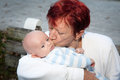 Grandmother kissing grandson holding infant outside Royalty Free Stock Image