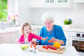 Grandmother and little girl making salad beautiful senior lady happy loving healthy for lunch with her granddaughter cute curly in Royalty Free Stock Image