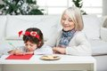 Grandmother looking at boy writing letter to santa claus during christmas home Stock Photos