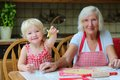 Grandmother making cookies together with granddaughter loving caring beautiful senior woman baking tasty sweet her cute little Stock Photo