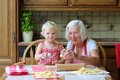 Grandmother making cookies together with granddaughter loving caring beautiful senior woman baking tasty sweet her cute little Stock Images