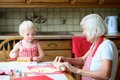 Grandmother making cookies together with granddaughter loving caring beautiful senior woman baking tasty sweet her cute little Royalty Free Stock Photography