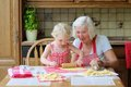 Grandmother making cookies together with granddaughter loving caring beautiful senior woman baking tasty sweet her cute little Royalty Free Stock Photos