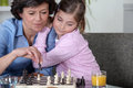 Grandmother playing chess with little girl Stock Images