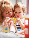 Grandmother playing with her grandson happy having fun and solving puzzle little cute Stock Photo