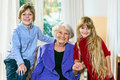 Grandmother posing with her two grandchildren smiling elderly grey haired sitting flanked by a happy little blond boy and girl in Stock Photography