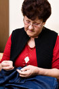 Grandmother sewing trousers on the couch Stock Images