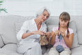 Grandmother teaching granddaughter how to knit in the living room Royalty Free Stock Image