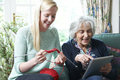 Grandmother Using Digital Tablet Whilst Granddaughter Knits Royalty Free Stock Photo