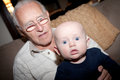 Grandpa and grandson baby sitting on his grandfather s lap image orientation is horizontal there is copy space Stock Photo
