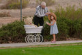 Grandpa helping little girl with hat on walk with toy buggy Royalty Free Stock Photo