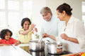 Grandparents and grandchildren cooking meal at home in kitchen chatting Royalty Free Stock Photos