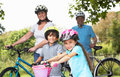Grandparents and grandchildren on cycle ride in countryside smiling to camera Royalty Free Stock Photo