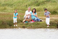 Grandparents and grandchildren having picnic on riverbank smiling Royalty Free Stock Image