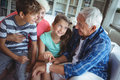 Grandparents and grandchildren looking at smartwatch in living room Royalty Free Stock Photo