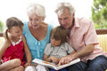 Grandparents and grandchildren reading book on garden seat Stock Photo