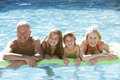 Grandparents And Grandchildren Relaxing In Swimming Pool Together