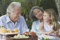 Grandparents with granddaughter at outdoor table sitting garden Stock Image
