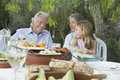 Grandparents with granddaughter at outdoor table sitting garden Stock Photography