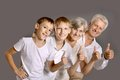 Grandparents with grandkids showing thumbs up on grey background Stock Image