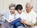 Grandparents and grandson reading a book together Royalty Free Stock Photos
