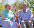 Grandparents happy with their grandson sitting outside Stock Images
