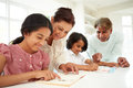 Grandparents helping children with homework pointing at book Stock Photo