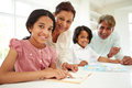 Grandparents helping children with homework smiling to camera Royalty Free Stock Image