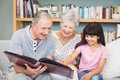 Grandparents showing album to granddaughter Royalty Free Stock Photo