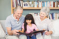 Grandparents showing album to granddaughter at home Royalty Free Stock Photo