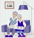 Grandparents sitting on the couch and looking photo book. Royalty Free Stock Photo