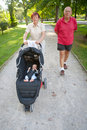 Grandparents walking baby in the park a grandmother grandfather and stroller on a sunny summer day Royalty Free Stock Photography