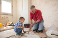 Grandsonis helping to his grandfather in separating the old parqet Royalty Free Stock Photo