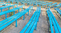 Grandstand old stadium empty wooden benches of blue color are on Stock Images